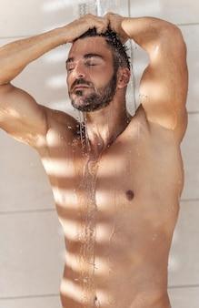 Os raios do sol em um homem tomando banho pela manhã. um homem alto e bonito com músculos toma banho depois de nadar. um homem sexy e nu está na cabana e lava o cabelo