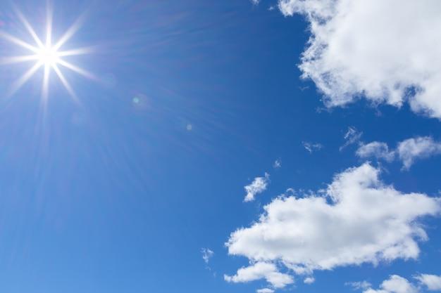 Os raios do sol no céu azul com nuvens cumulus.