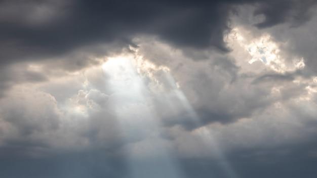 Os raios do sol penetram pelas nuvens escuras durante o pôr do sol, panorama