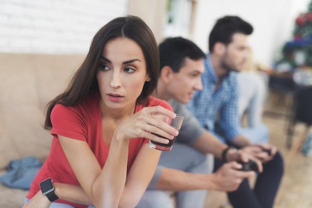 Os rapazes e duas raparigas jogam na consola de jogos