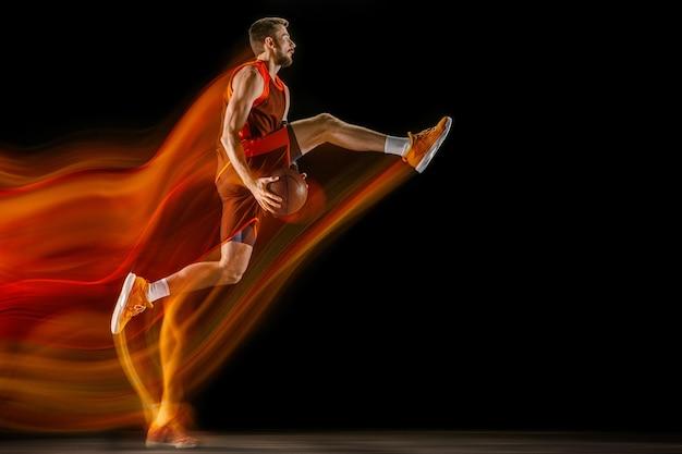 Os rastros de fogo. jovem jogador de basquete caucasiano do time vermelho em ação