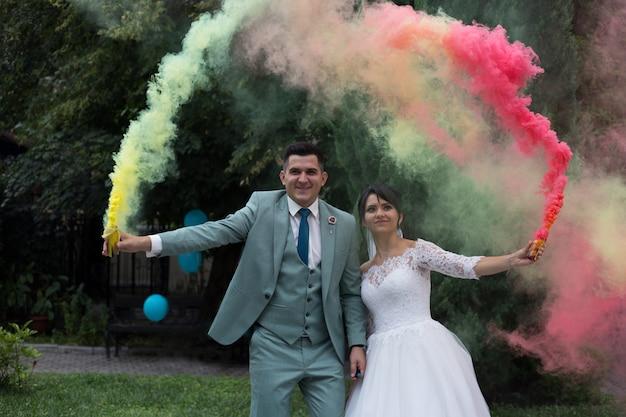 Os recém-casados acendem bombas de fumaça coloridas. fumaça colorida