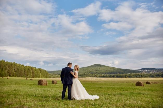 Os recém-casados andam e relaxam no campo, casamento