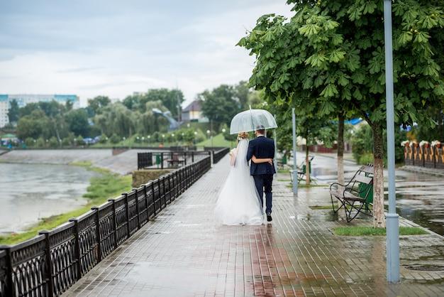 Os recém-casados andam sob um guarda-chuva na chuva no parque