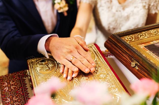 Os recém-casados colocaram as mãos com os anéis de casamento no livro sagrado e trocaram seus votos