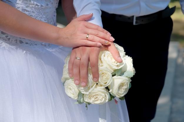 Os recém-casados colocaram as mãos no buquê. closeup vista