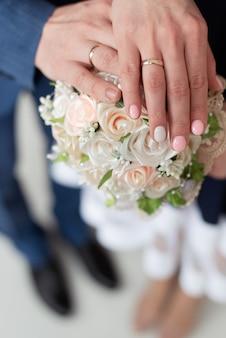 Os recém-casados dão as mãos e mostram as alianças, um buquê de casamento. mãos e anéis em um buquê de casamento