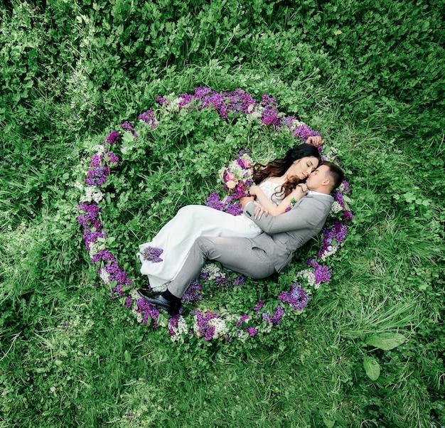 Os recém-casados estão no círculo de lilás no gramado verde