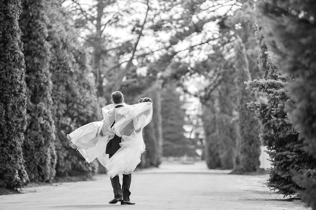 Os recém-casados felizes vão descansar. noivo segurando sua noiva. jovem carregando sua noiva nos braços.