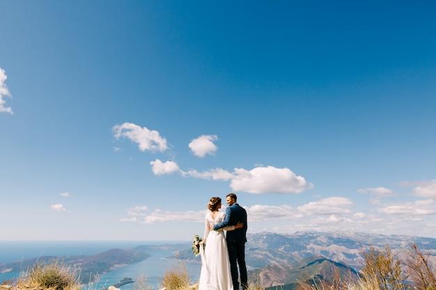Os recém-casados ficam de costas abraçados contra o pano de fundo das montanhas e um céu azul brilhante