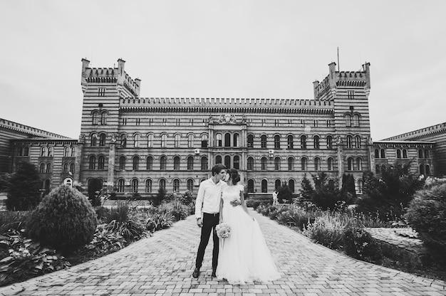 Os recém-casados ficam perto de uma arquitetura restaurada, um prédio, uma casa antiga do lado de fora e um palácio vintage ao ar livre. amor romântico na rua de atmosfera vintage. foto em preto e branco.