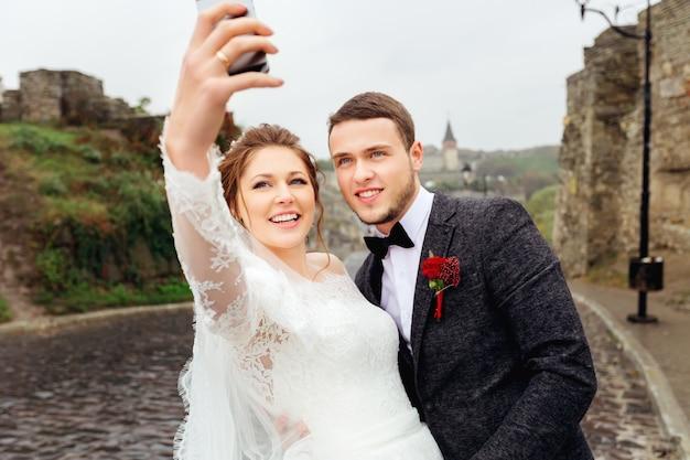Os recém-casados se fotografam em um telefone celular no fundo da cidade velha