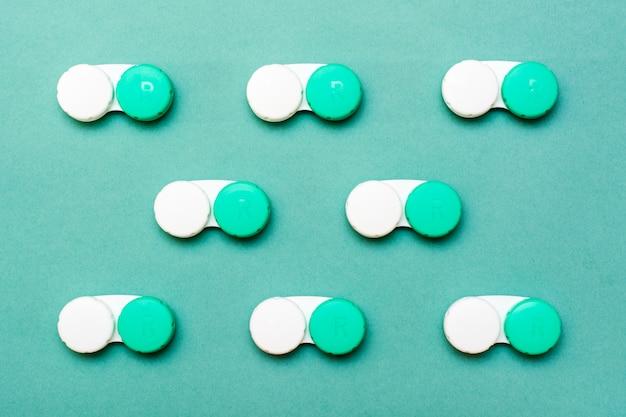 Os recipientes para lentes encontram-se em linhas organizadas sobre um fundo verde.