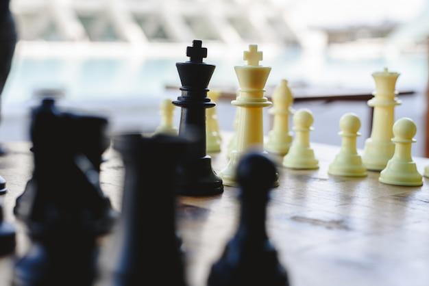 Os reis preto e branco da xadrez enfrentaram entre partes defocused na placa de madeira.
