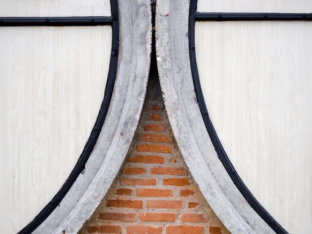 Os restos da parede de tijolos antigos fazem a parede perto da parede de madeira branca