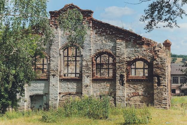 Os restos de uma casa de pedra abandonada e abandonada coberta de musgo e coberta de árvores em uma floresta