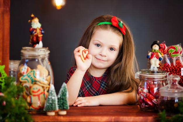 Os retratos de uma linda garotinha perto de decorações de natal com pão de mel