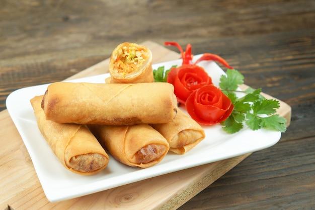 Os rolos de mola chineses fritados serviram com molho de pimentão e tomates cor-de-rosa decorados com verde com folhas na madeira, espaço. comida asiática de conceito