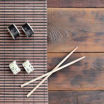 Os rolos de sushi e os chopsticks de madeira encontram-se em uma esteira de serwing de bambu da palha. comida asiática tradicional. vista do topo