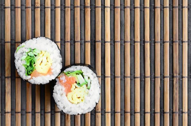 Os rolos de sushi encontram-se em uma esteira de serwing de bambu da palha. comida asiática tradicional.