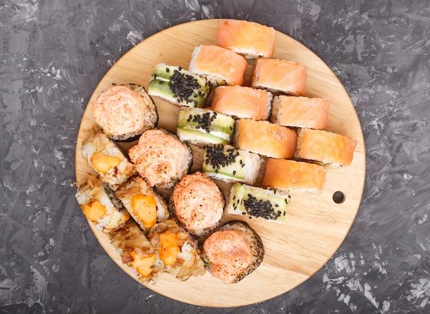 Os rolos de sushi japoneses misturados do maki ajustaram-se no fundo concreto preto, vista superior.