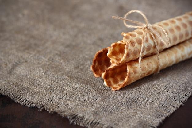 Os rolos de wafer são ocos sem encher o barbante amarrado no pano de saco cinza e em uma bancada escura. doce confeitaria.