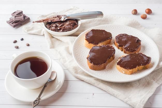 Os sanduíches com avelã do chocolate espalharam na placa. xícara de café na mesa.