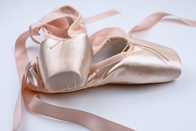 Os sapatos de balé de cetim rosa colocam, mostram detalhes, para a prática