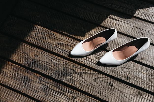 Os sapatos de casamento da noiva estão em um piso de madeira ao ar livre