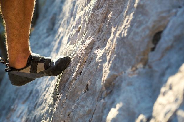 Os sapatos de escalada no pé do alpinista apoiam o dedo do pé na rocha. esportes radicais, turismo de montanha. fechar-se. copie o espaço. perna de homem peluda