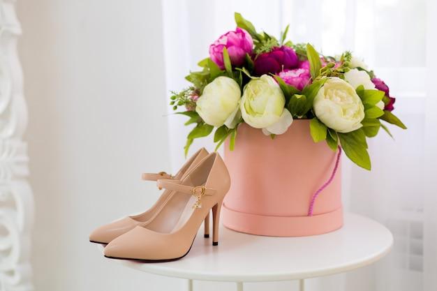 Os sapatos de salto alto bege das mulheres bonitas estão sobre uma mesa branca, ao lado de uma caixa redonda com peônias coloridas