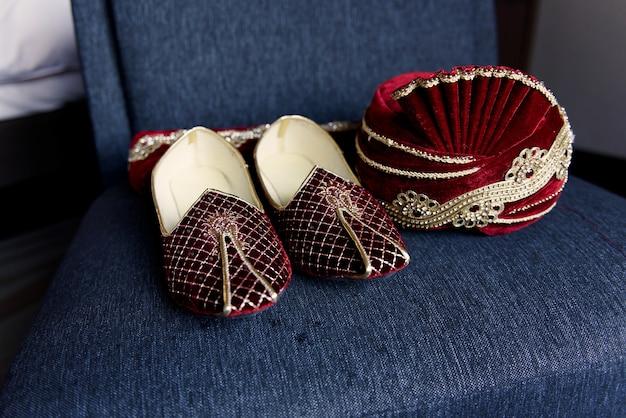 Os sapatos e o chapéu do noivo do vermelho indiano encontram-se na cadeira azul