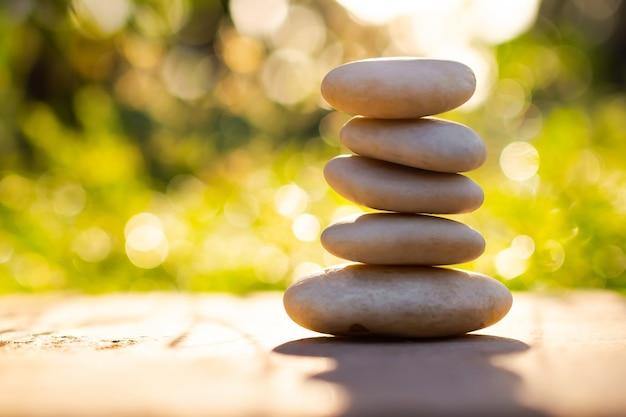 Os seixos da pirâmide na natureza ao ar livre de madeira desfocam o fundo do bokeh. empilhar pedra zen velha para estabilidade, equilíbrio, calma, meditação, budismo ou conceito de spa de terapia de aroma.