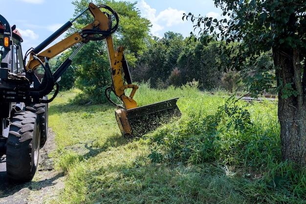 Os serviços rodoviários estão envolvidos em um trator com um cortador mecânico que corta a grama ao lado da estrada de asfalto