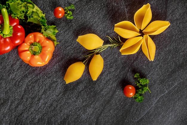 Os shell secam a massa com pimentão e tomates. cozinha italiana.