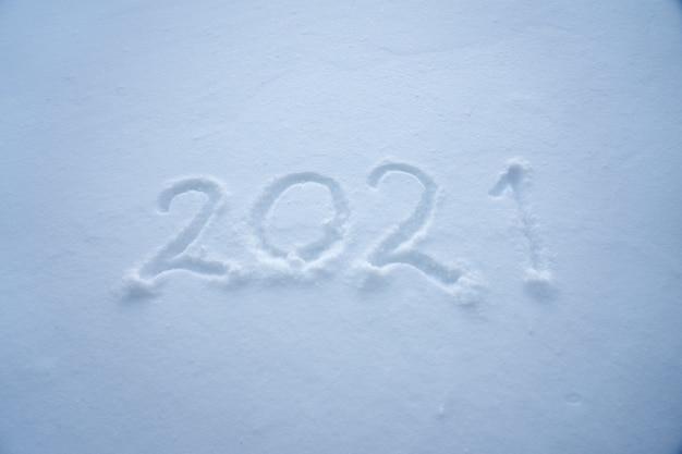 Os símbolos numéricos do ano novo de 2021 estão escritos na neve. copie o espaço.