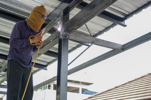 Os soldadores estão soldando a armação de telhado de aço da casa