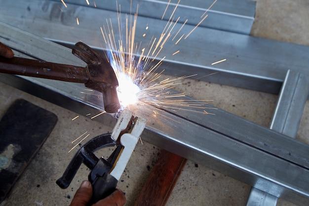 Os soldadores estão soldando aço na fábrica