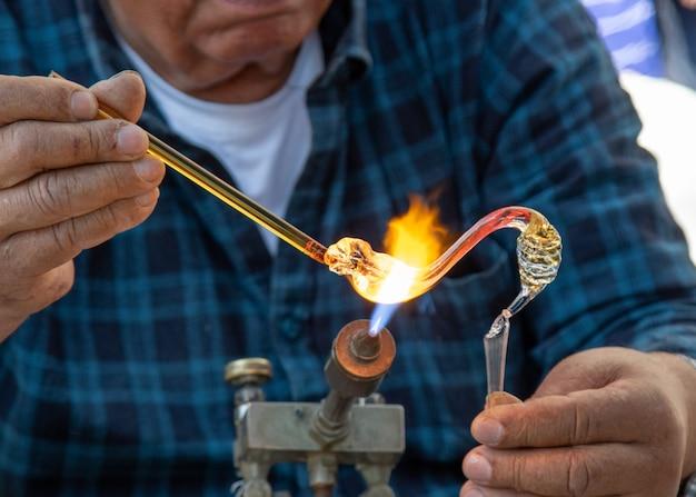 Os sopradores de vidro masculinos fazem produtos artesanais sob o queimador de gás.
