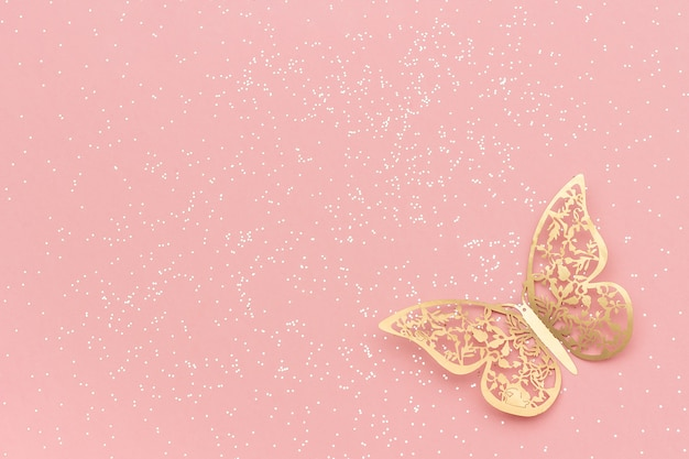 Os sparkles brilham e borboleta do tracery do ouro no fundo na moda pastel cor-de-rosa.