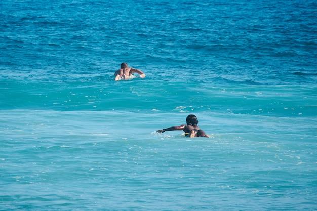 Os surfistas do homem branco e da mulher negra nadam na formação. vista traseira. lifestule.
