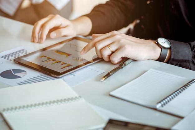 Os tablet pc do uso do homem de negócios para conectar com a palavra para analisam o comércio da economia. ele é casado. ele tocou na tela.