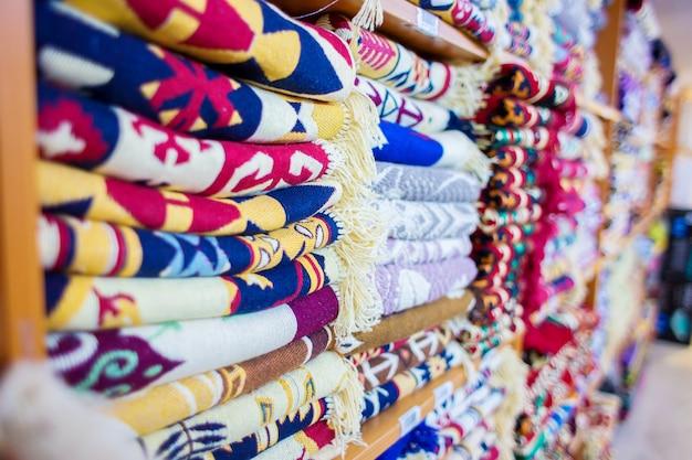 Os tapetes turcos estão à venda na loja. produtos estão encurtados em prateleiras de loja