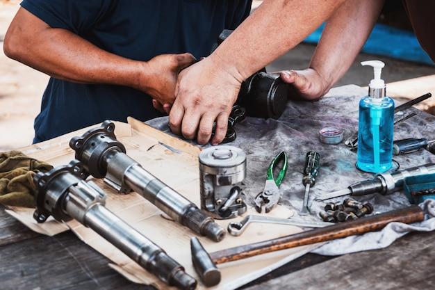 Os técnicos estão ajudando a montar a caixa de velocidades da direção hidráulica do carro. Foto Premium