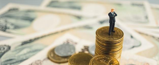 Os ternos do homem de negócios do líder estão entre a pilha de moeda e de dinheiro.