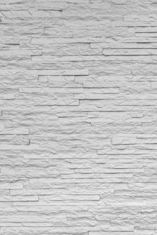 Os tijolos de pedra clássicos brancos são dispostos de acordo com o padrão da parede para um fundo bonito e simples.