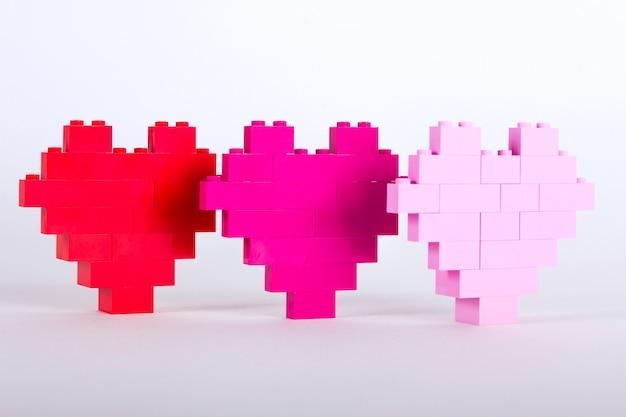 Os tijolos do construtor de plástico na forma de corações são vermelho, magenta, rosa. fundo branco.