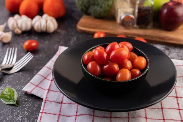 Os tomates estão no copo preto
