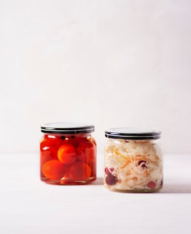 Os tomates fermentados e o repolho estão em pequenos potes sobre uma mesa de concreto.