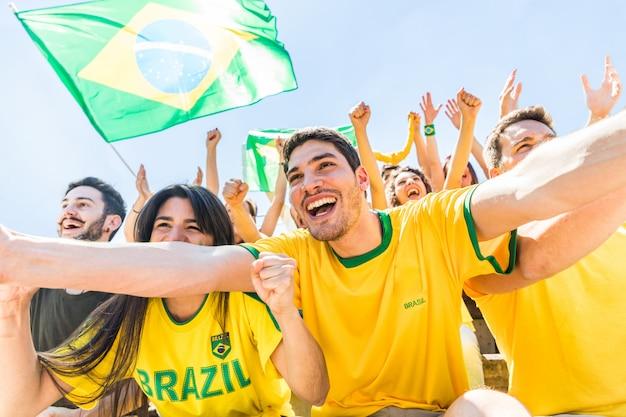 Os torcedores brasileiros comemorando no estádio com bandeiras